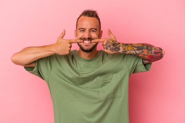 ピンクの背景に分離された入れ墨を持つ若い白人男性は、口に指を指して微笑んでいます。
