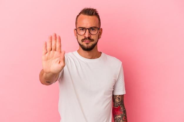 ピンクの背景に分離された入れ墨を持つ若い白人男性は、一時停止の標識を示している手を伸ばして立って、あなたを妨げています。