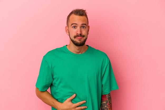 ピンクの背景に分離された入れ墨を持つ若い白人男性はおなかに触れ、優しく微笑み、食事と満足の概念。