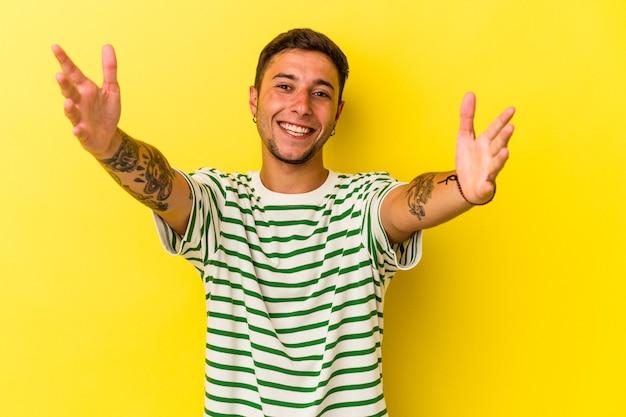 黄色の背景に分離された入れ墨を持つ若い白人男性は、カメラに抱擁を与えることに自信を持っています。