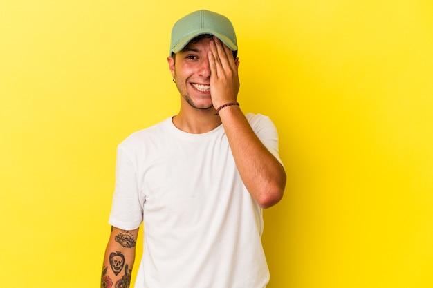 手のひらで顔の半分を覆うことを楽しんで黄色の背景に分離された入れ墨を持つ若い白人男性。