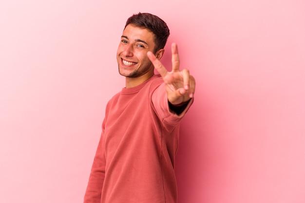 黄色の背景に分離された入れ墨を持つ若い白人男性は、指で平和のシンボルを示して楽しくてのんきです。