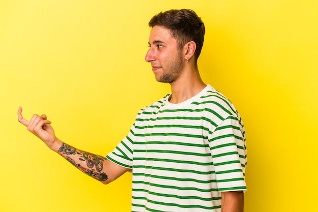 誘うようにあなたに指で指している黄色の背景に分離された入れ墨を持つ若い白人男性が近づいています。