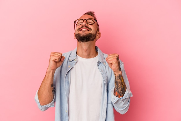 Young caucasian man with tattoos isolated on pink background  celebrating a victory, passion and enthusiasm, happy expression.
