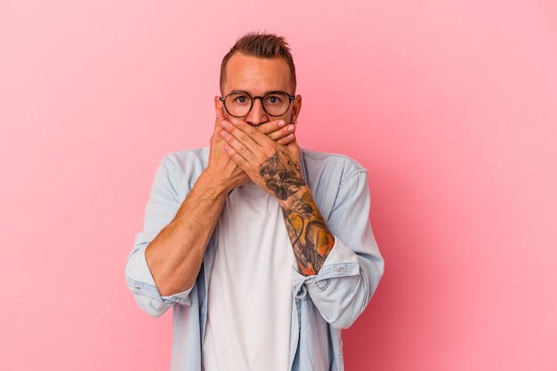 Young caucasian man with tattoos isolated on pink background  covering mouth with hands looking worried.