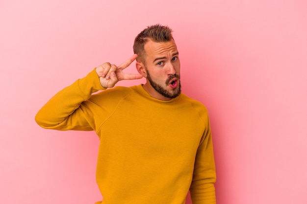 Young caucasian man with tattoos isolated on pink background  dancing and having fun.