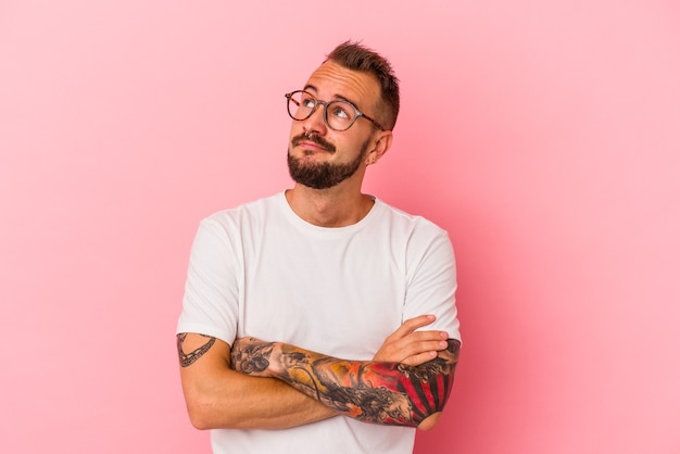 Young caucasian man with tattoos isolated on pink background  dreaming of achieving goals and purposes