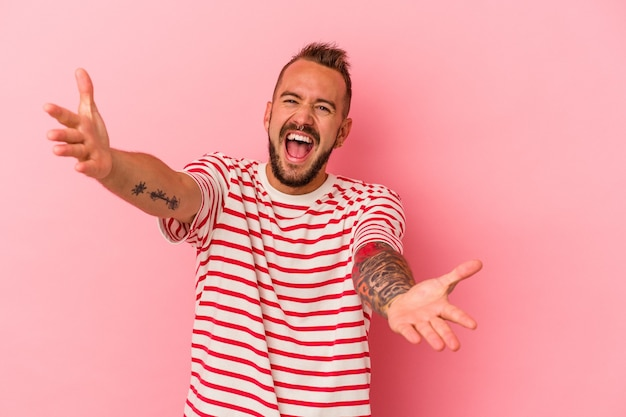 Young caucasian man with tattoos isolated on pink background  feels confident giving a hug to the camera.