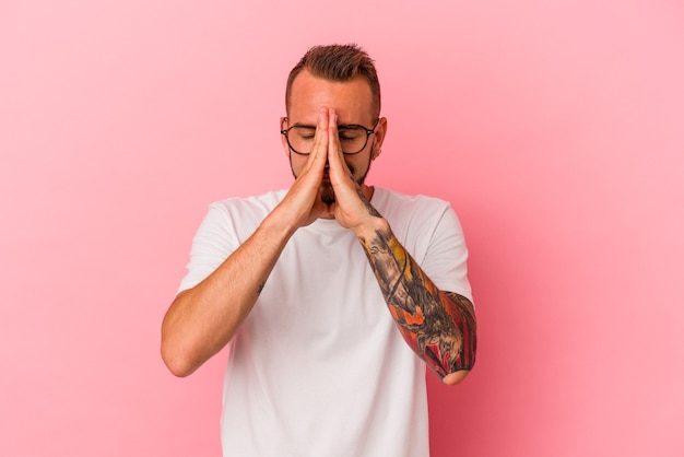 Young caucasian man with tattoos isolated on pink background  holding hands in pray near mouth, feels confident.