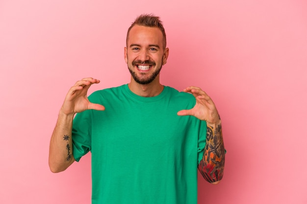 Young caucasian man with tattoos isolated on pink background  holding something with palms, offering to camera.