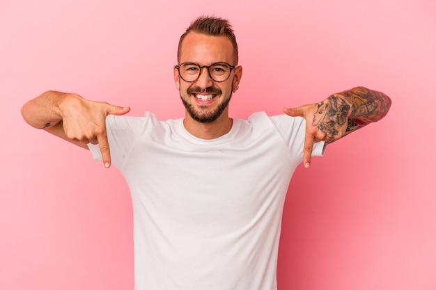 Young caucasian man with tattoos isolated on pink background  points down with fingers, positive feeling.
