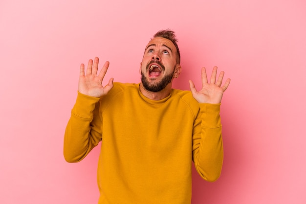 Young caucasian man with tattoos isolated on pink background  screaming to the sky, looking up, frustrated.