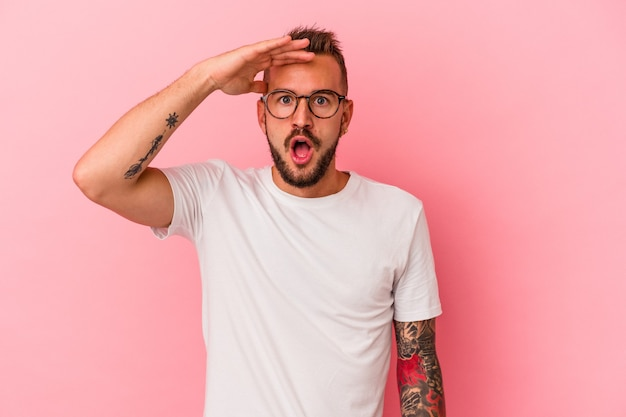 Young caucasian man with tattoos isolated on pink background  shouts loud, keeps eyes opened and hands tense.