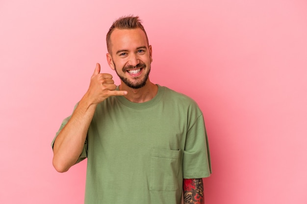 Young caucasian man with tattoos isolated on pink background  showing a mobile phone call gesture with fingers.