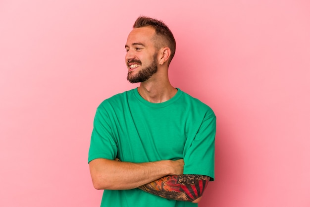 Young caucasian man with tattoos isolated on pink background  smiling confident with crossed arms.