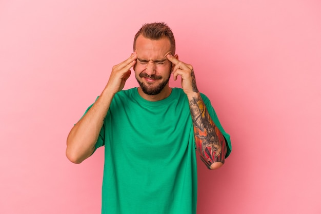 Young caucasian man with tattoos isolated on pink background  touching temples and having headache.