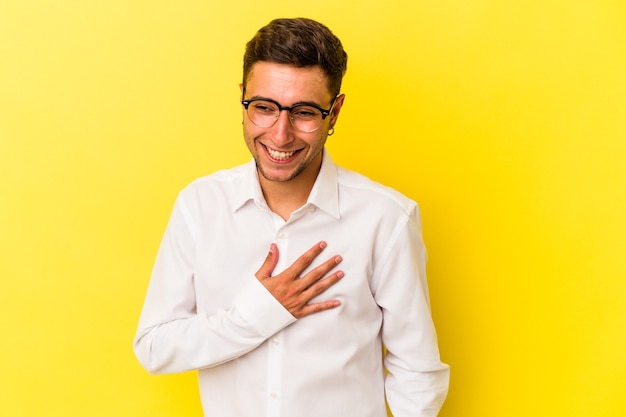Young caucasian man with tattoos isolated on yellow background  laughing keeping hands on heart, concept of happiness.