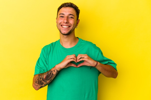 Young caucasian man with tattoos isolated on yellow background  smiling and showing a heart shape with hands.