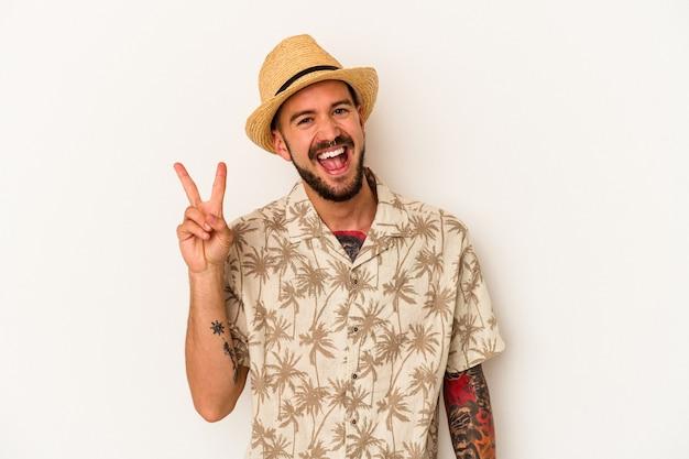 指で平和のシンボルを示す白い背景に分離された夏の服を着て楽しくてのんきな入れ墨を持つ若い白人男性。