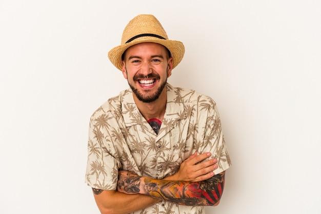 笑って楽しんでいる白い背景で隔離の夏服を着ている入れ墨を持つ若い白人男性。