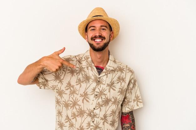 誇りと自信を持って、シャツのコピースペースを手で指している白い背景の人に分離された夏服を着ている入れ墨を持つ若い白人男性