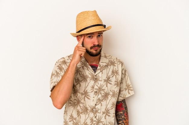 指で寺院を指して、思考、タスクに焦点を当て、白い背景で隔離の夏服を着ている入れ墨を持つ若い白人男性。