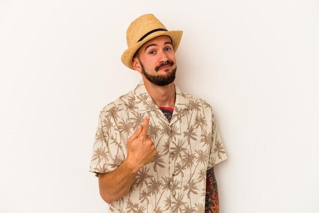 誘うようにあなたに指で指している白い背景で隔離の夏服を着ている入れ墨を持つ若い白人男性が近づいてくるように。