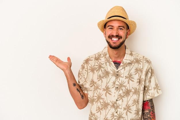 手のひらにコピースペースを示し、腰に別の手を保持している白い背景で隔離の夏服を着ている入れ墨を持つ若い白人男性。