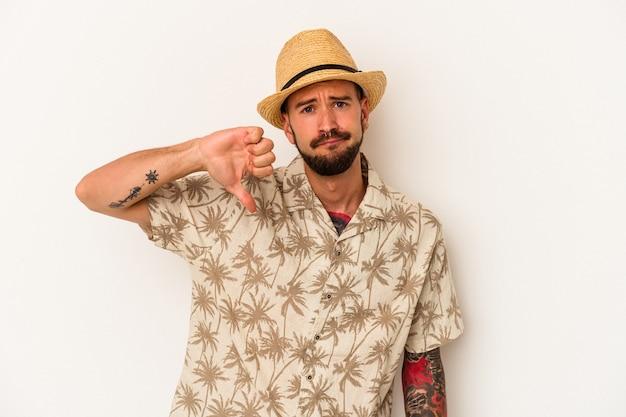 嫌いなジェスチャーを示す白い背景で隔離の夏服を着ている入れ墨を持つ若い白人男性は、親指を下に向けます。不一致の概念。
