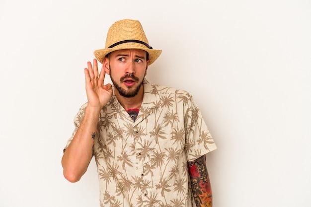 ゴシップを聴こうとしている白い背景で隔離の夏服を着ている入れ墨を持つ若い白人男性。