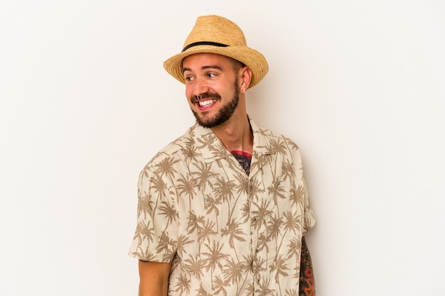 Young caucasian man with tattoos wearing summer clothes isolated on white background  looks aside smiling, cheerful and pleasant.