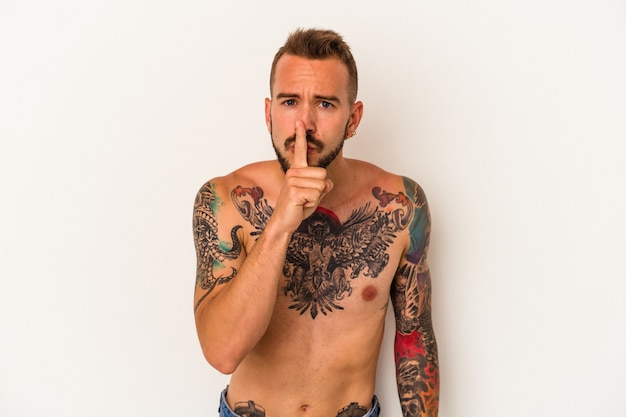Young caucasian man without t-shirt isolated on white background  keeping a secret or asking for silence.