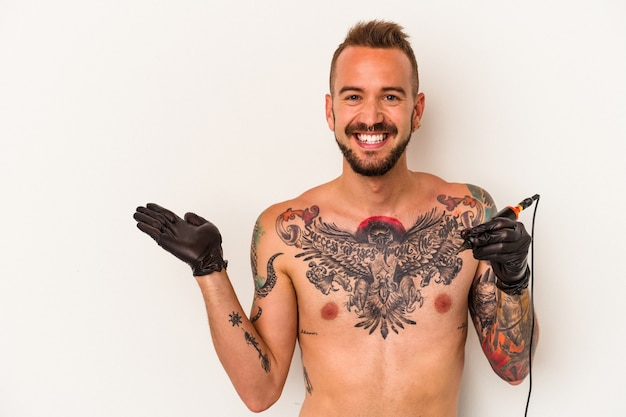 Young caucasian man without t-shirt isolated on white background  showing a copy space on a palm and holding another hand on waist.