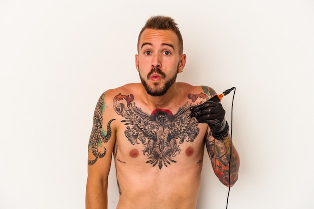 Young caucasian man without t-shirt isolated on white background  shrugs shoulders and open eyes confused.
