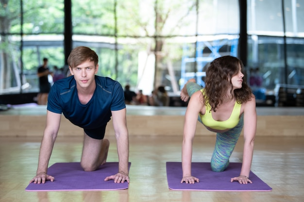 Young caucasian man and woman in yoga class room fitness training