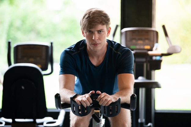 Young caucasian man work out on bicycle machine in fitness room at gym