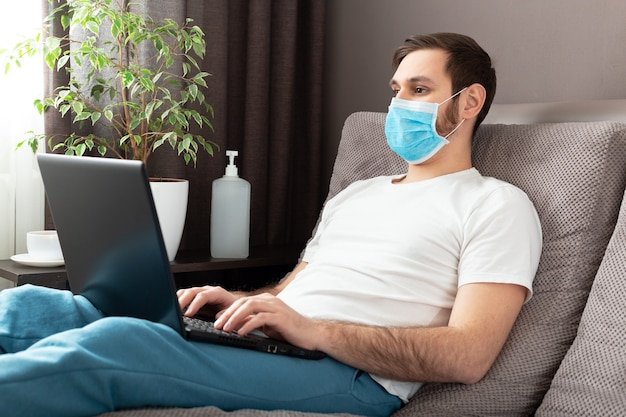 Young caucasian man working from home wearing protective mask using laptop and internet. cozy home office, workplace on sofa during coronavirus pandemic, covid-19 quarantine. remote work, freelancer.