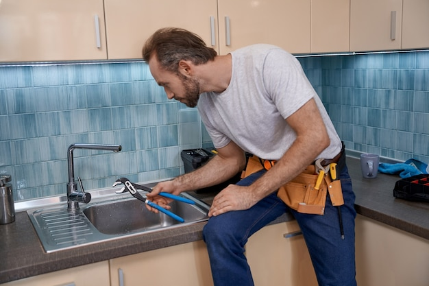Young caucasian man working with sink sitting on tabletop