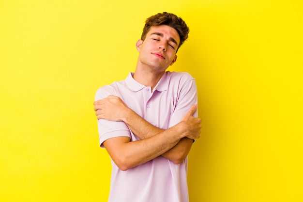Young caucasian man on yellow hugs, smiling carefree and happy.