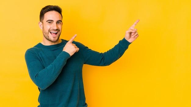 Young caucasian man on yellow wall dancing and having fun.