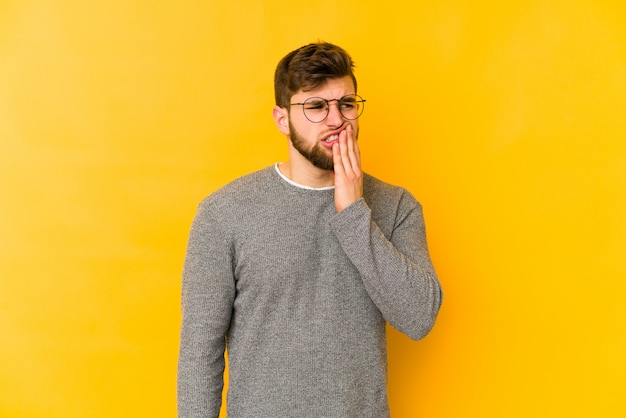 Young caucasian man on yellow wall having a strong teeth pain