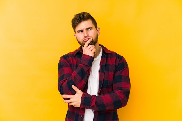 Young caucasian man on yellow wall looking sideways with doubtful and skeptical expression.