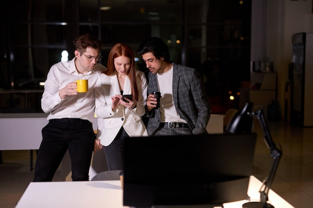 Young caucasian men and woman colleagues having rest after work in office, use smartphone, watching something interesting, leisure time after hard working day, stand together in formal wear