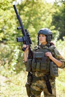 젊은 백인 군사 여자는 자연에서 그녀의 손에 총을 들고, 그녀는 사냥을 할 것이고, 숲에서 사냥은 취미입니다. 무기로 게임