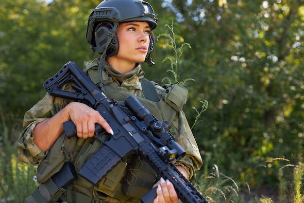 Young caucasian military woman holds a gun in her hand in nature