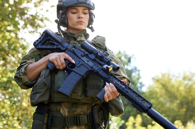 Young caucasian military woman is checking rifle in the forest before shooting