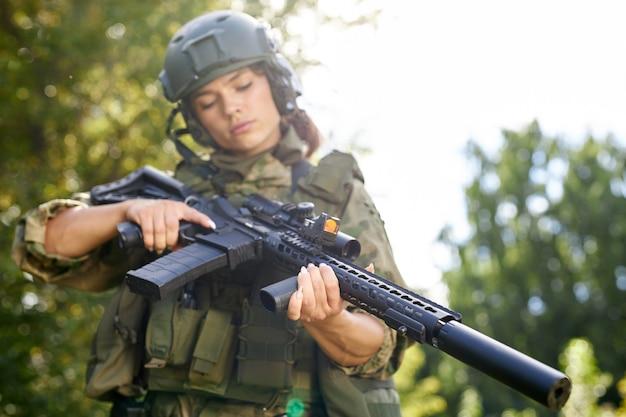 若い白人軍の女性は、撮影する前に森の中でライフルをチェックしています