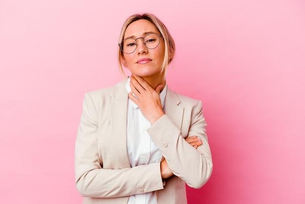 Молодая кавказская бизнес-леди смешанной расы, изолированная на розовом, страдает от боли в горле из-за вируса или инфекции.
