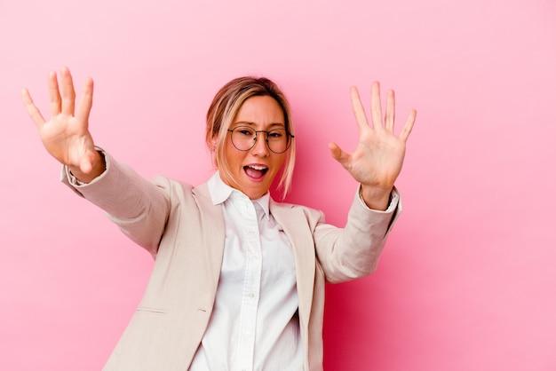 임박한 위험으로 인해 충격을 받고 분홍색 벽에 고립 된 젊은 백인 혼혈 비즈니스 여자