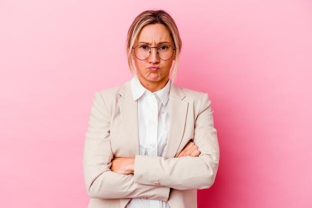 분홍색 벽에 고립 된 젊은 백인 혼혈 비즈니스 여자 불면 뺨, 피곤식이있다. 표정 개념.